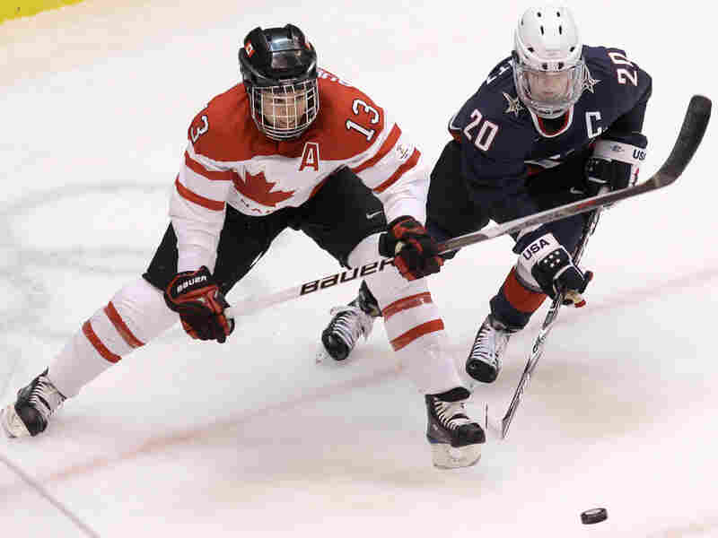 Canada's Caroline Ouellette and USA's Natalie Darwitz on the ice Thursday.  Julie Jacobson/AP