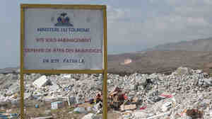 A sign on Haiti's  National Road 2, now surrounded by rubble, instructs people not to throw garbage.