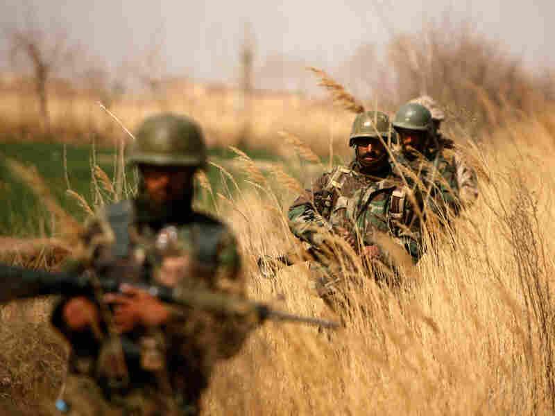 Afghan National Army soldiers patrol outside Marjah