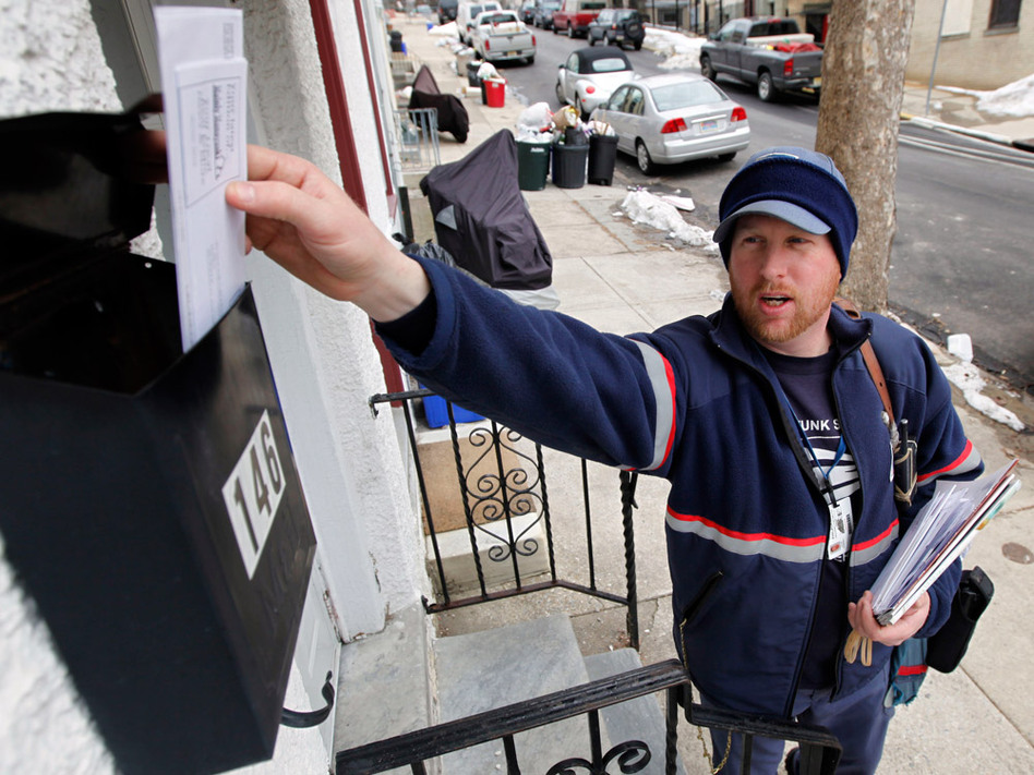 Letter carrier Kevin Pownall delivers mail in Philadelphia. The U.S. Postal Service is considering reducing its six days of home delivery as a cost-saving measure. (Matt Rourke/AP)