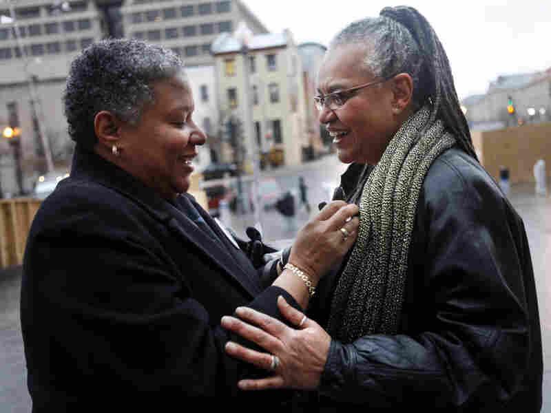 Candy Holmes (left) affixes a marriage equality pin to her partner, Darlene Garner.