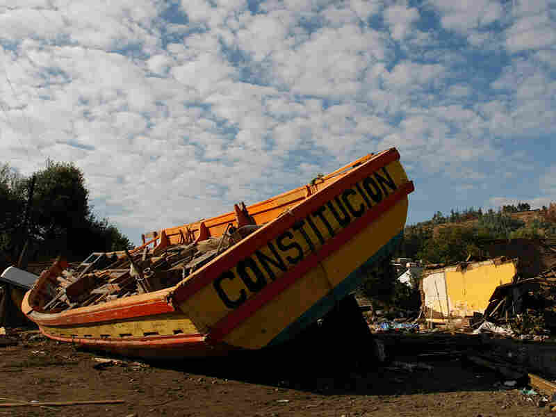A boat battered by quake-triggered waves was driven ashore near the port in Constitucion, Chile.