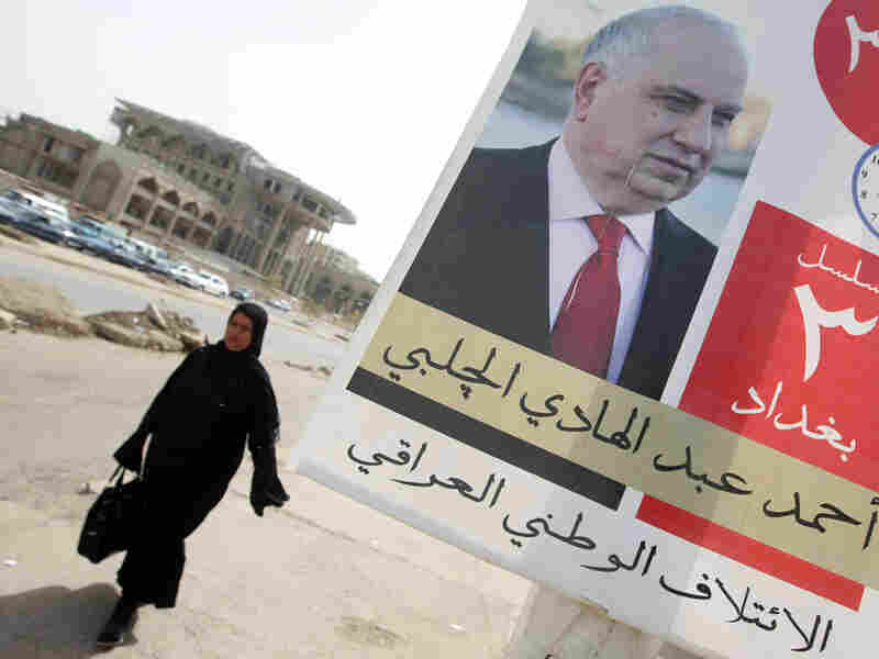 An Iraqi woman walks past an election campaign poster bearing a picture of Ahmed Chalabi.