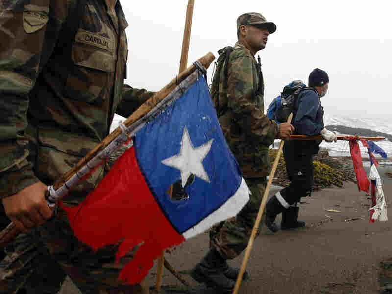 Soldiers and rescue workers carrying damaged Chilean flags search for victims.