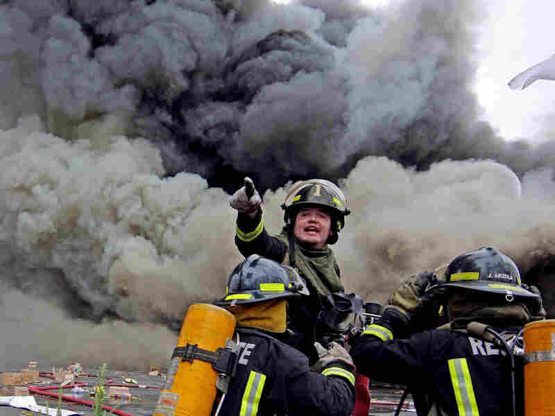 Firefighters try to control a fire at a supermarket burned by looters in Concepcion, Chile.