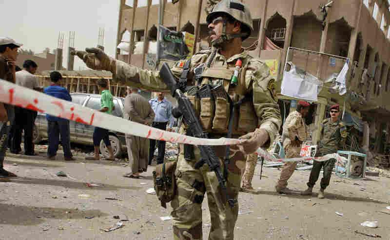 Iraqi security forces secure the scene where a blast killed seven in Baghdad's Hurriya neighborhood.