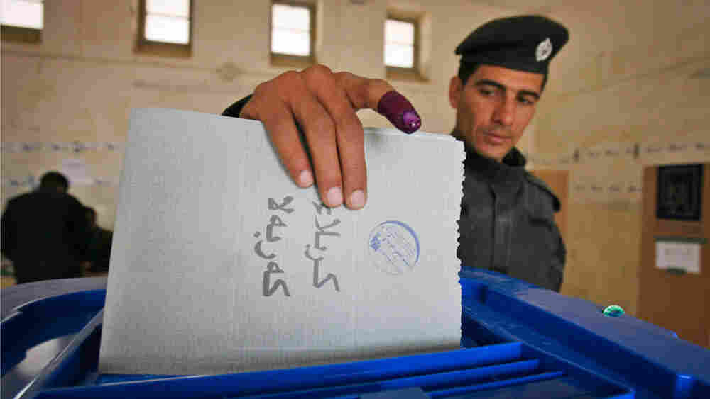 An Iraqi policeman casts his vote at a polling center in Karbala on Thursday.