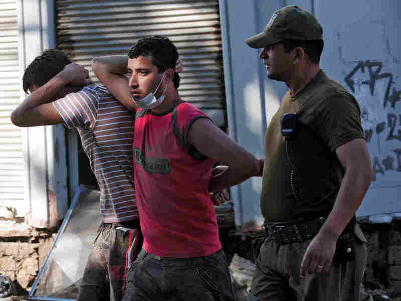 A soldier escorts two men detained for looting on Tuesday in the fishing village of Constitucion.