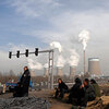Workers rest in front of the cooling towers of a coal-fired power plant in Dadong, Shanxi .