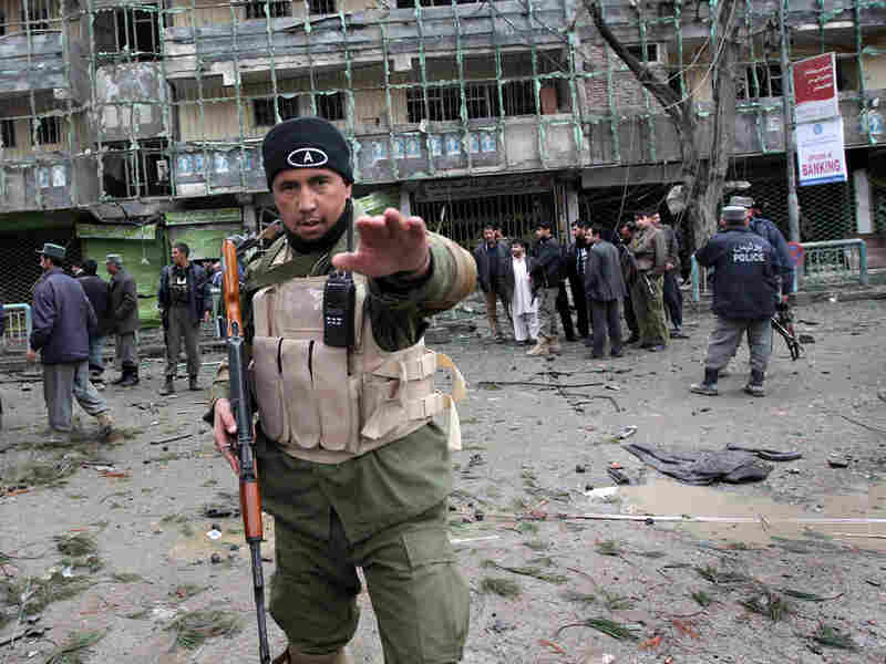 An Afghan security officer tries to stop photographers from taking pictures in Kabul.