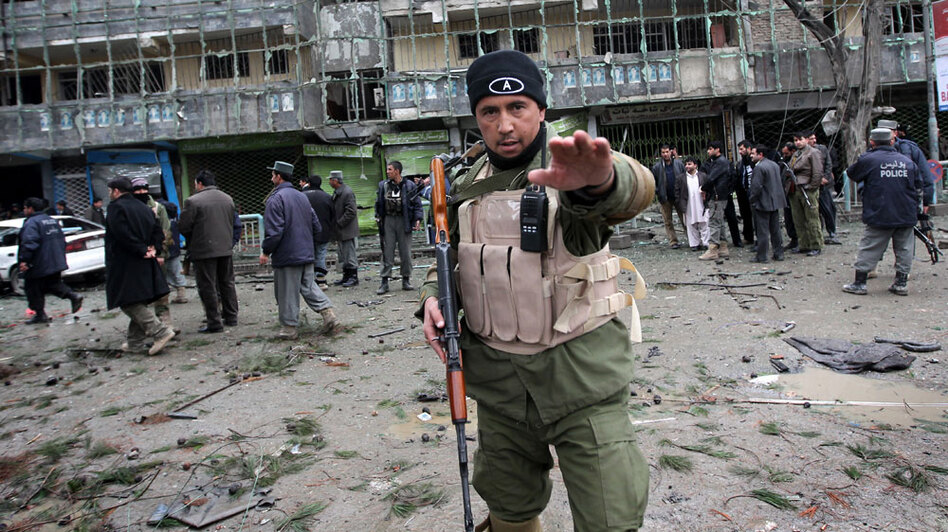 An Afghan security officer tries to stop photographers from taking pictures outside The Park Residence guesthouse at the site of a gun battle in the Shar-e Naw district in Kabul on Feb. 26.