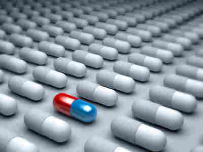 An red and blue pill amid many gray pills lined up.