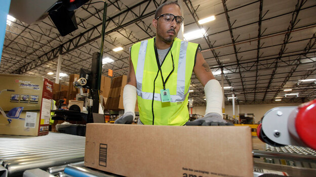 Reginal Armstead Jr. sends a package from an Amazon.com warehouse in Goodyear, Ariz., in November 2009. When consumers in some states buy items through Internet merchants, they avoid being charged state sales tax. (AP)