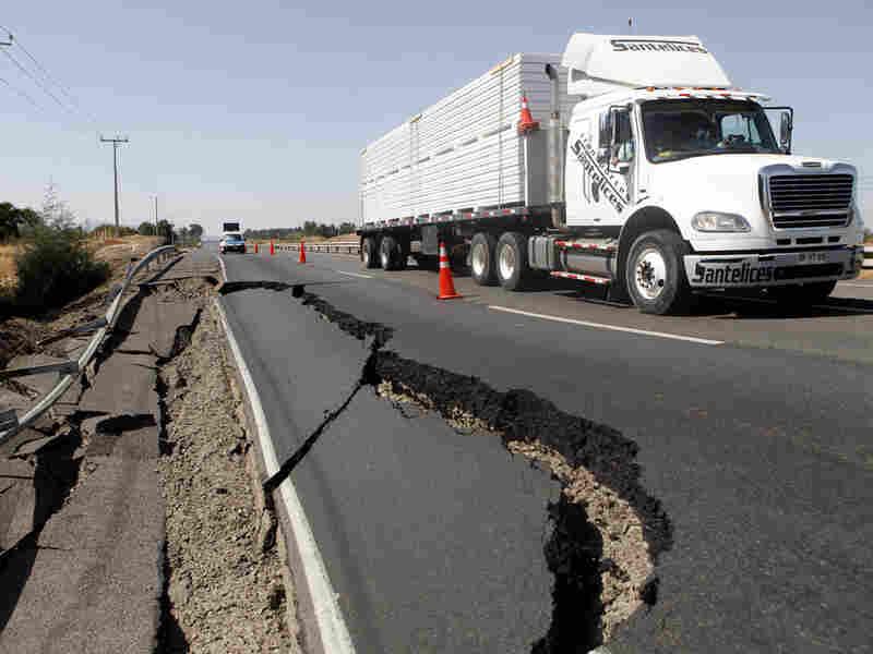 A truck passes damage on a road near San Rafael