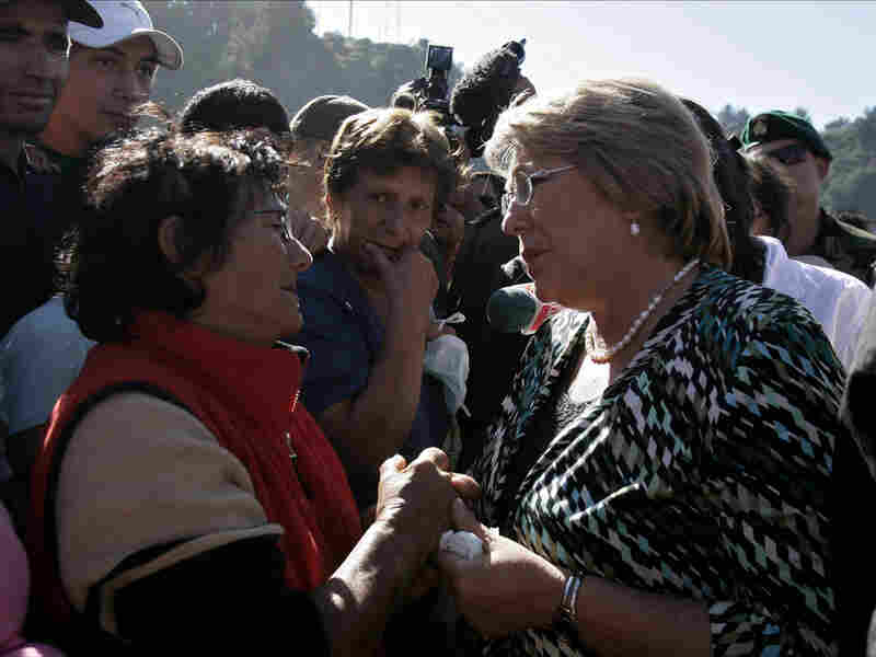 Chilean President Michelle Bachelet (right) speaks to am earthquake survivor