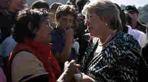 Chilean President Michelle Bachelet (right) speaks to am earthquake survivor