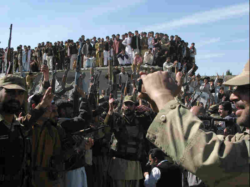 Militia members brandish weapons while dancing in a show of force in Khar, the main town in the trib