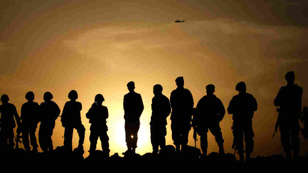 Afghan Army commandos stand on a sand bank at sunset in Marjah.