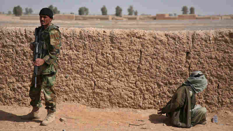 An Afghan National Army soldier stands guard over a blindfolded suspected Taliban fighter.