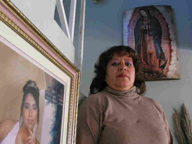 Olga Esparza Rodriguez stands next to a photo of her daughter, Monica, who disappeared last year