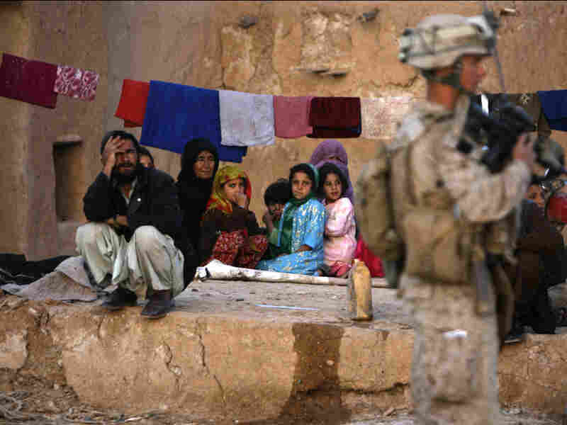 A U.S. Marine office guards an Afghan family in Trikh Nawar.