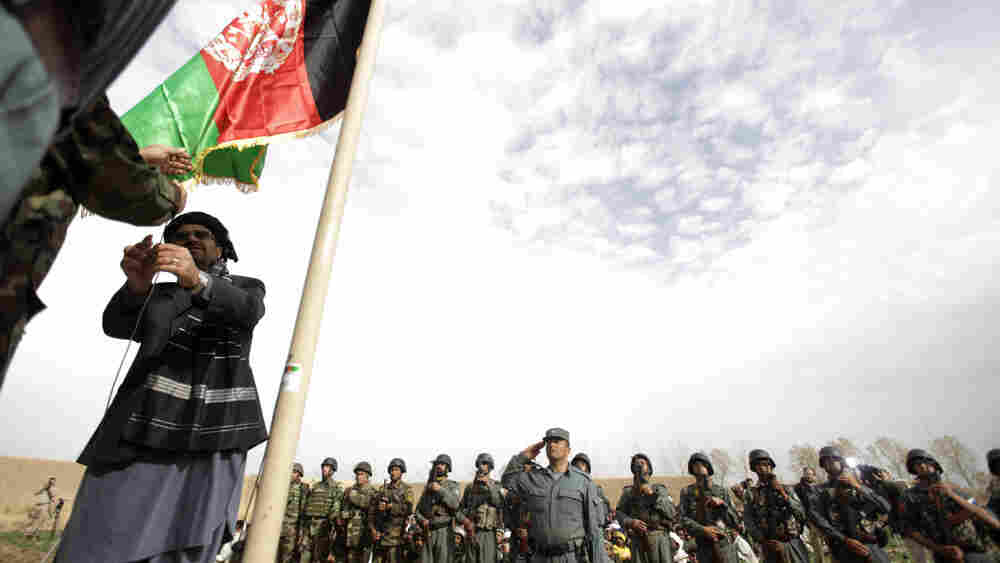 Gulab Mangal, Helmand province's governor, hoists the Afghan flag in Marjah.