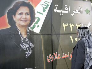 An Iraqi man looks at a campaign billboard