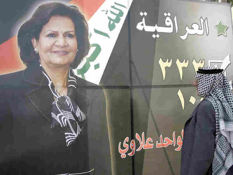 An Iraqi man looks at a campaign billboard