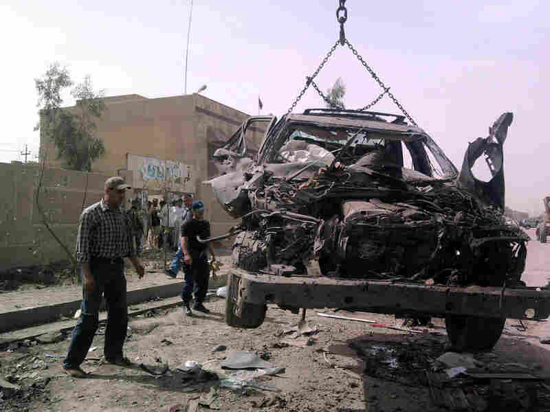A vehicle is removed from the scene of a double-blast suicide bomb in Fallujah, Iraq.