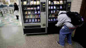 A student buys something from a vending machine.