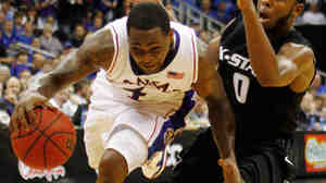 Kansas guard Sherron Collins (4) drives past Kansas State guard Jacob Pullen (0).