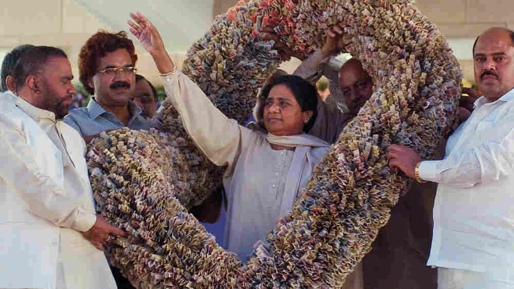 Uttar Pradesh state Chief Minister Mayawati waves after being presented a garland made of money