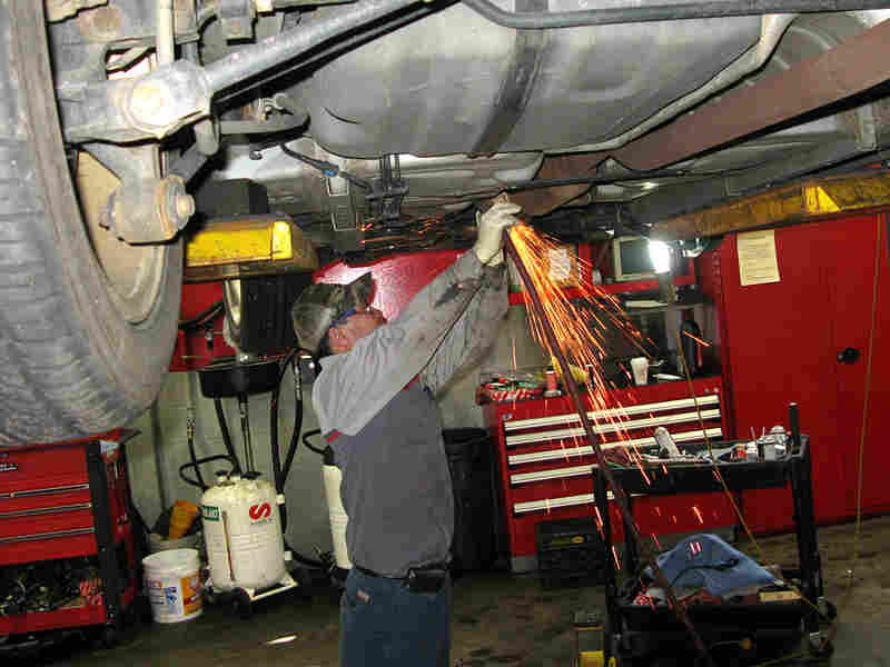 A mechanic works on a Toyota in a repair bay at the Expressway Toyota dealership.