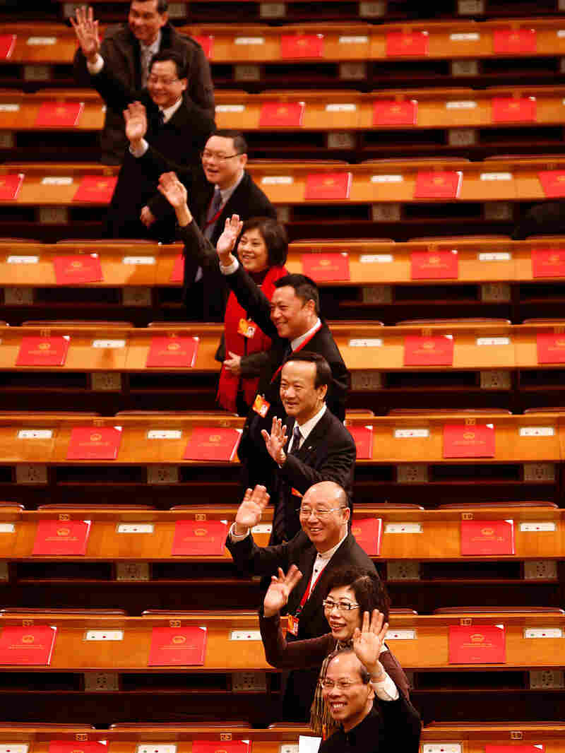 Delegates gesture as they arrive for a session Sunday of the National People's Congress