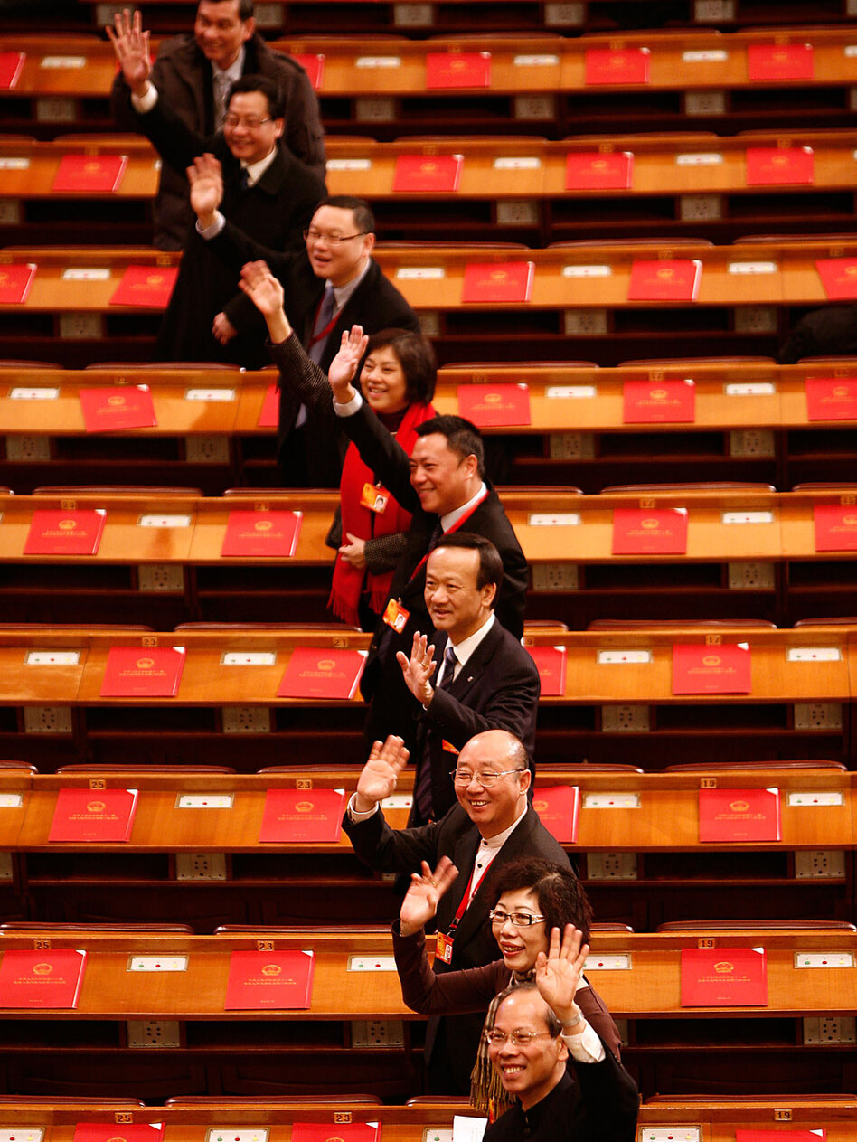 "Delegates gesture as they arrive for a session March 14 of the National People's Congress in Beijing. Historian Lei Yi says that when Chinese now say ""we've been represented,"" it means they're aware that they have actually been misrepresented."
