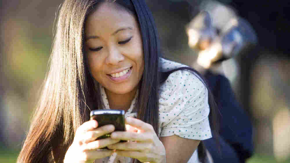 A student checking her mobile phone on campus.
