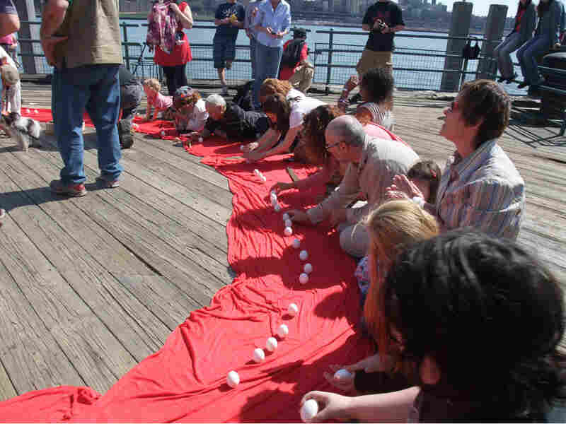 New Yorkers balance eggs at the South Street Seaport Saturday. Margot Adler/NPR