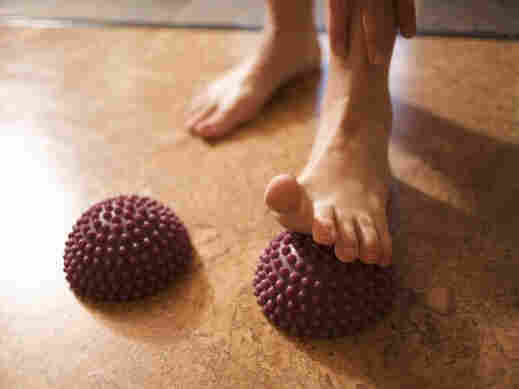 A woman rolling her foot on a stretching ball.