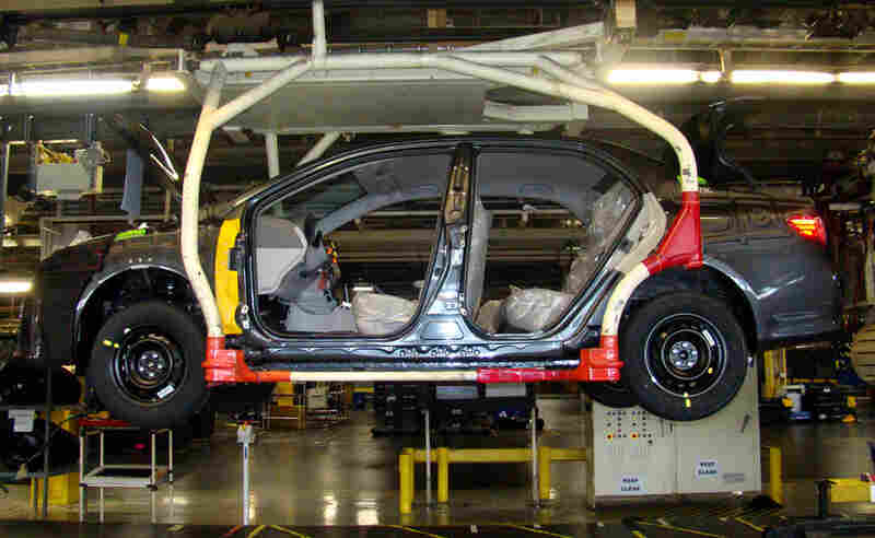 A car moves down the auto assembly line at New United Motor Manufacturing Inc.