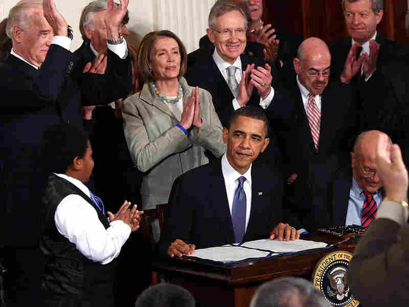 Democrats applaud President Obama's signing of the health care overhaul into law.