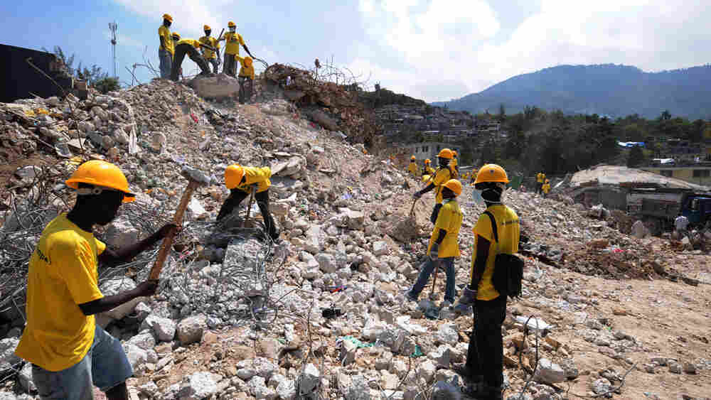 Workers remove rubble from a destroyed school in Port-Au-Prince.