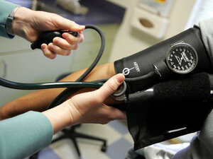 A doctor takes her patient's blood pressure.