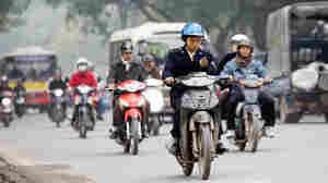 Motorcyclist checks cell phone in Hanoi