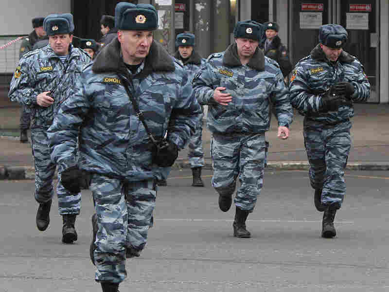 Russian riot police run near the Lubyanka metro station