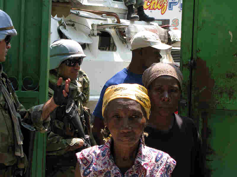Women in Port-au-Prince wait for tarps and water jugs being handed out