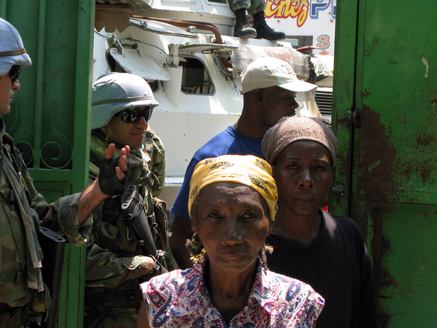 Women in Port-au-Prince wait for tarps and water jugs being handed out by the International Organization for Migration. U.N. troops provide essential security for such aid distribution efforts.