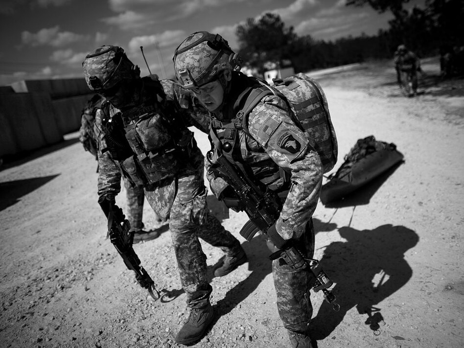 Sgt. 1st Class Armando Prescott (left) and Pfc. Jeffery Rigdin pull a stretcher after a mock gun battle with a simulated casualty from Delta Company.