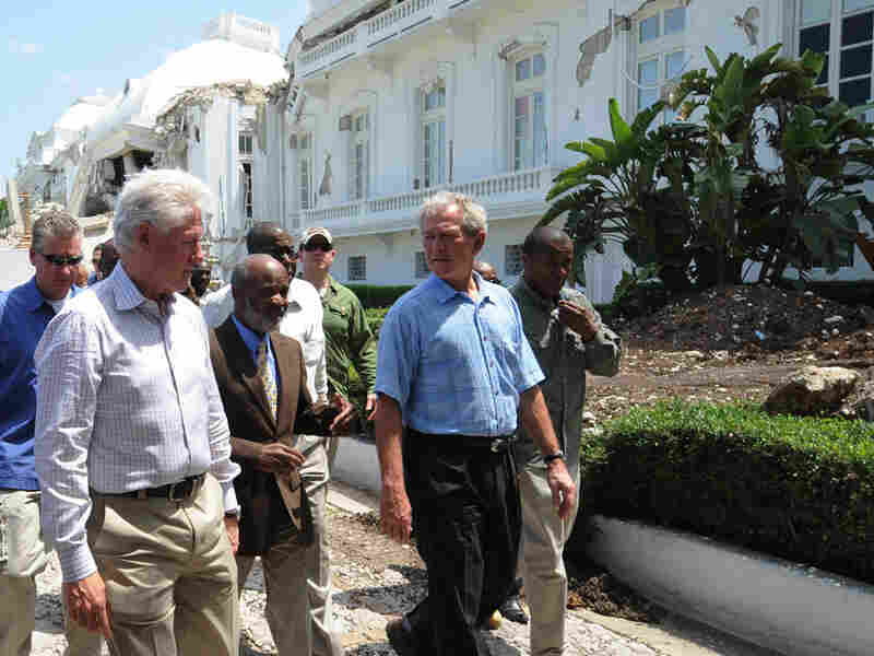 Former U.S. presidents George Bush and Bill Clinton walk with Haitian President Rene Preval.
