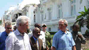 Former U.S. presidents George Bush and Bill Clinton walk with Haitian President Rene Preval.