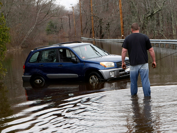 A tow truck operator checks on a car he is pulling out of a flooded road in Exeter, R.I., on Wednesday, March 31, 2010.